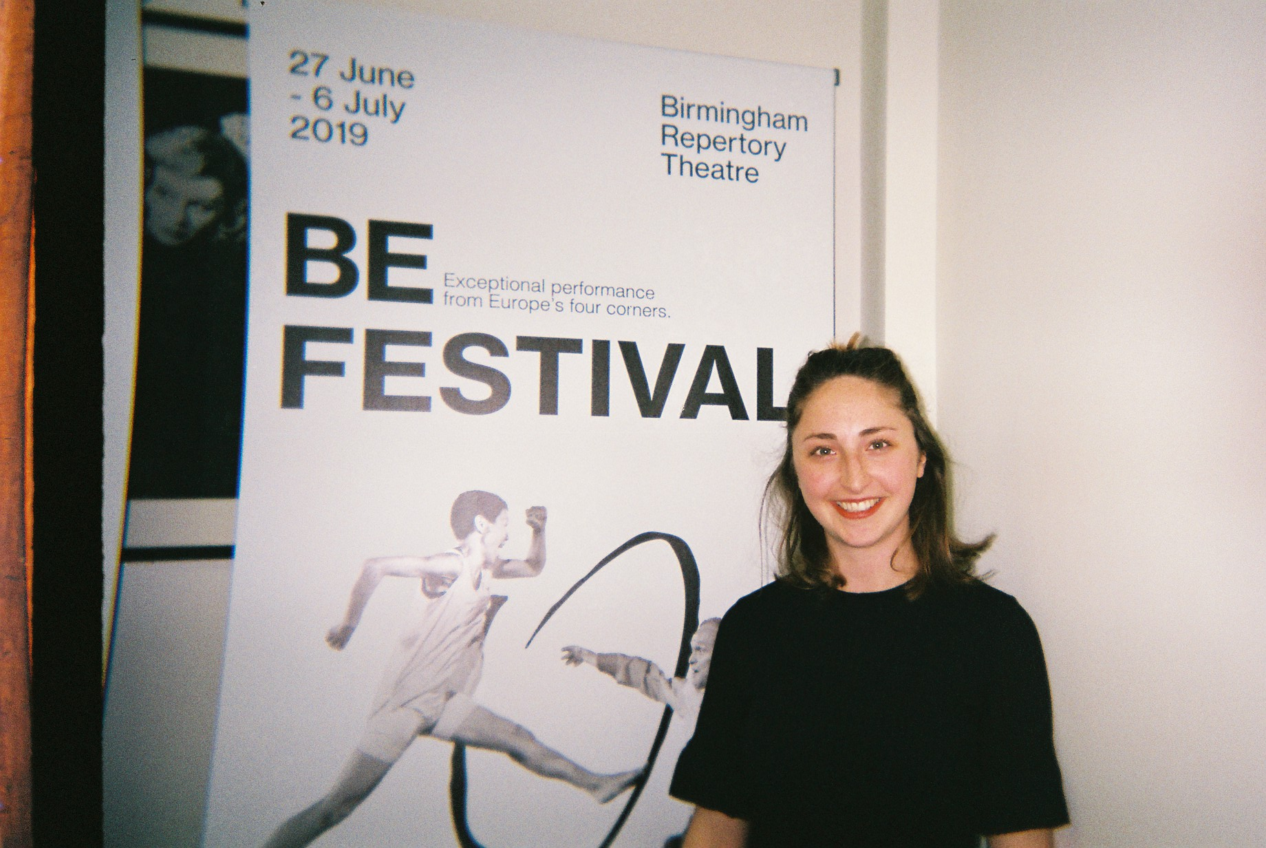 Cat Butler smiles in front of a BE Festival poster